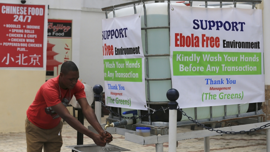 A man washes his hands at a tap outside the Green Pharmacy at Area 8 in Abuja, Nigeria.