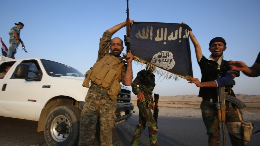 Iraqi Shiite fighters hold the Islamic State flag as a trophy as they celebrate after breaking the siege of Amerli by ISIS militants on September 1, 2014.