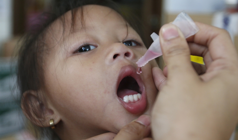 A girl receives anti-measles vaccination drops in Manila, the capital of the Philippines. Mass national vaccination campaigns against measles and polio are common in much of the developing world.