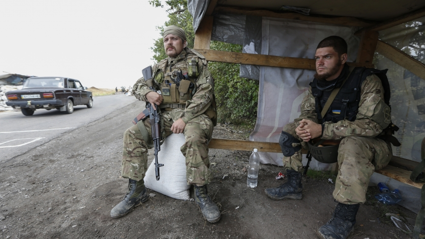 "Soldiers from the Ukrainian self-defence battalion ""Azov"" sit at a checkpoint in the southern coastal town of Mariupol on September 8, 2014."