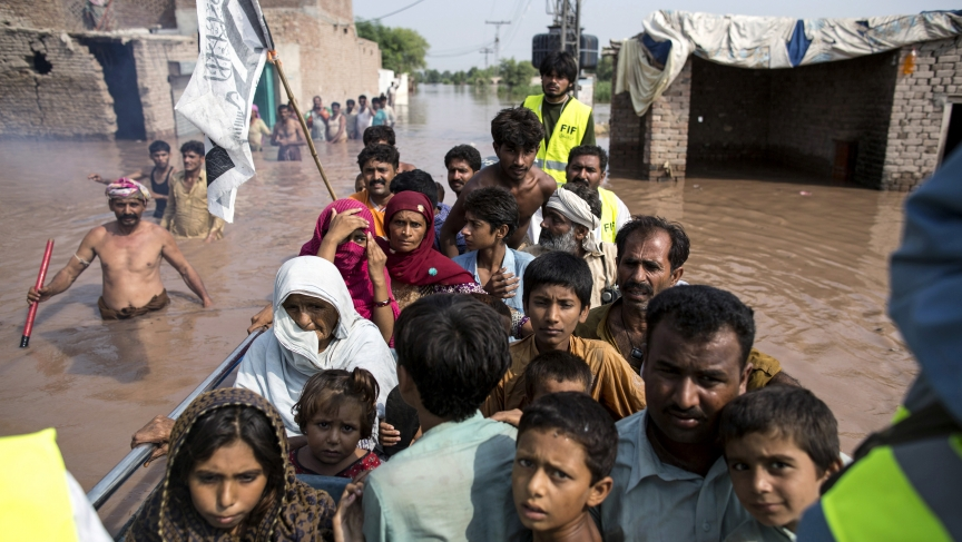 Punjabi flood victims are evacuated by boat from their flooded house following heavy rain in Jhang, Pakistan, on September 10, 2014.