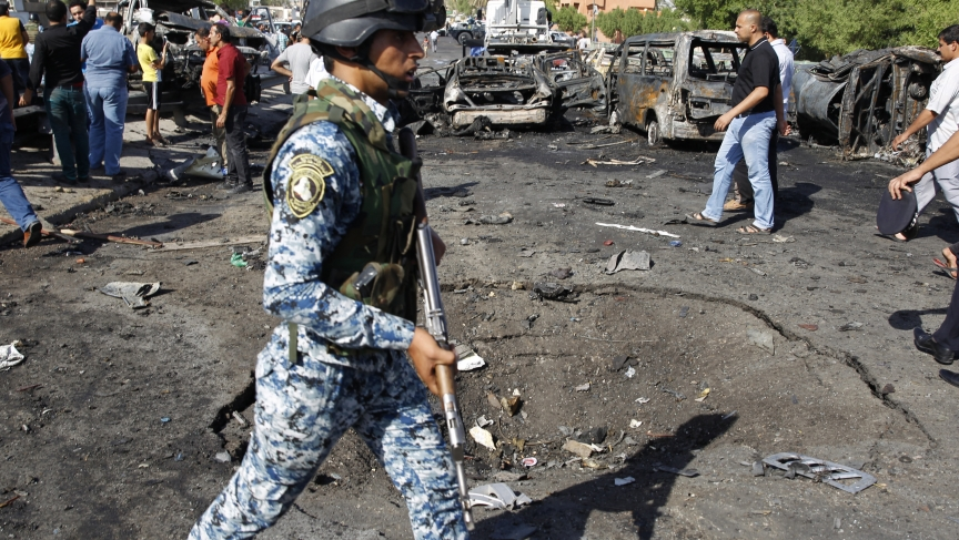 Iraqi security forces inspect the site of three explosions in the New Baghdad neighborhood on September 10, 2014.