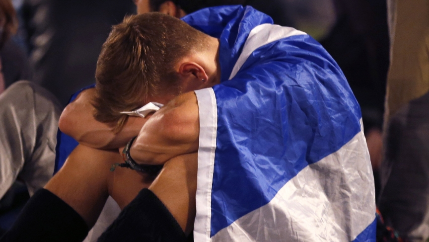 """A supporter from the """"Yes"""" Campaign cries into his knees as he sits in George Square in Glasgow, Scotland September 19, 2014. The """"Yes"""" Campaign bid to win independence for Scotland, failed."""