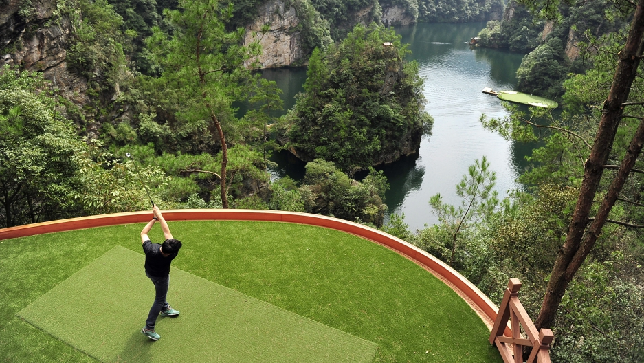 A staff member plays a shot towards a putting green on a lake from a tee ground on top of a hill, at Zhangjiajie, Hunan province September 23, 2014.