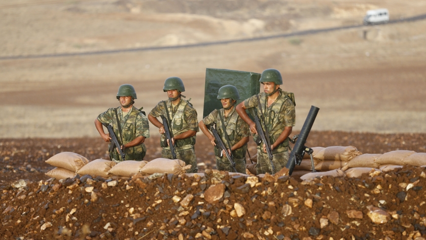 Turkish soldiers stand at a position on the Turkish-Syrian border near the southeastern town of Suruc on September 24, 2014.