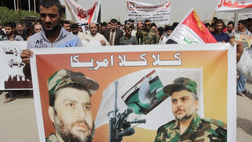 "A demonstrator holds a banner with a picture of Shiite cleric Moqtada al-Sadr during a protest against the entry of American troops into Iraq on September 26, 2014. The words on the banner read ""No No America."""