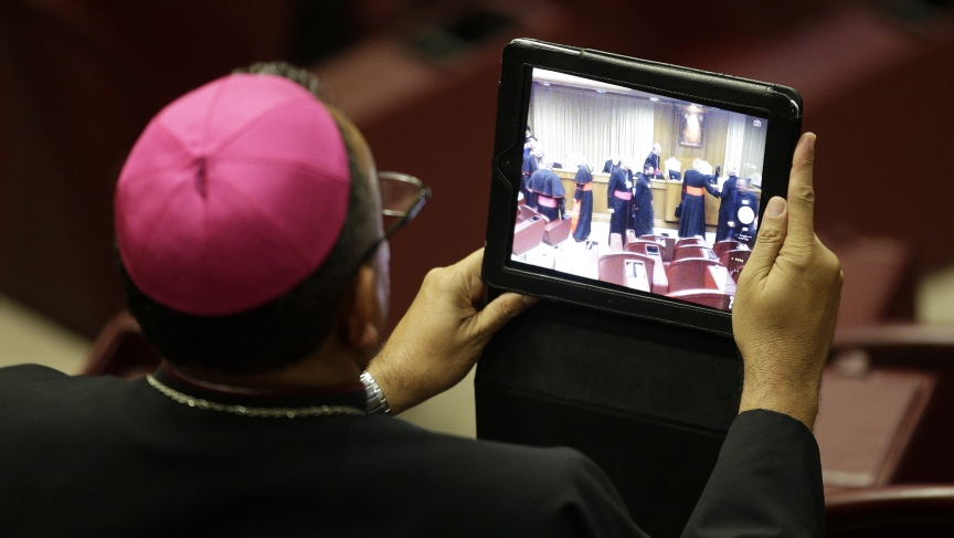 "A bishop takes a picture with a tablet during the Synod on the Family. The Roman Catholic assembly has softened its traditional Catholic stance against gays, suggesting ""accepting and valuing their sexual orientation."""