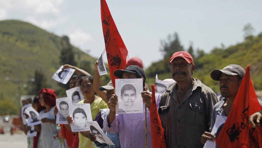 Relatives hold pictures of missing students during a demonstration demanding their safe return on the outskirts of Chilpancingo, Mexico, on October 7, 2014.