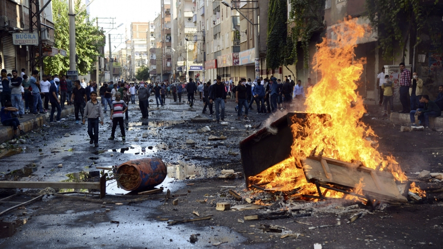 Kurdish protesters set fire to a barricade blocking the street as they clash with riot police in Diyarbakir, Turkey, on October 7, 2014.