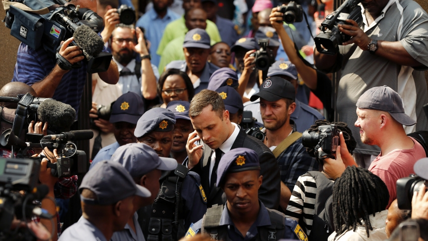Olympic and Paralympic track star Oscar Pistorius uses his phone as he leaves the first day of his sentencing at North Gauteng High Court in Pretoria on October 13, 2014.