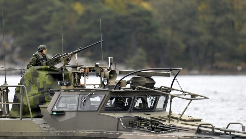 Crew members onboard a Swedish Navy fast-attack craft stand guard at the Stockholm archipelago during a hunt for a suspected Russian submarines on October 18, 2014.