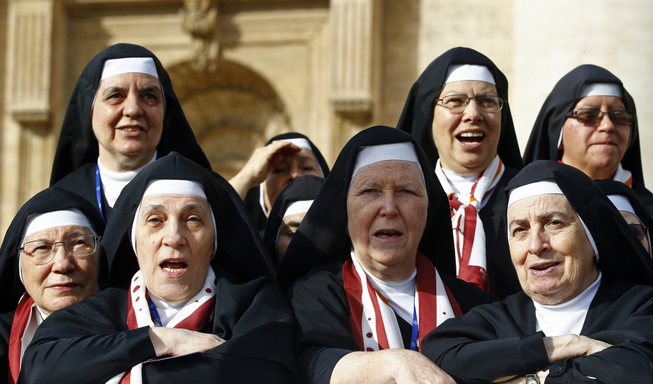 Nuns look on as Pope Francis arrives to lead his weekly audience in Saint Peter's Square at the Vatican on October 22, 2014.