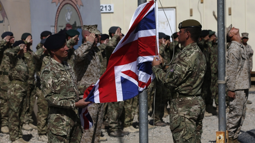 British troops lower the Union Flag during a ceremony marking the end of operations for US Marines and British combat troops in Helmand on October 26, 2014.