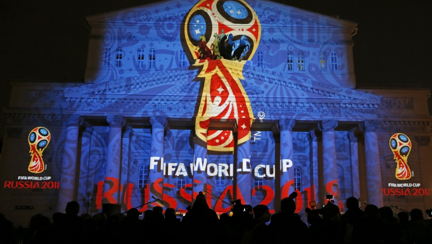 Journalists look at a light installation showing the official logotype of the 2018 FIFA World Cup during its unveiling ceremony at the Bolshoi Theater building in Moscow, October 28, 2014.