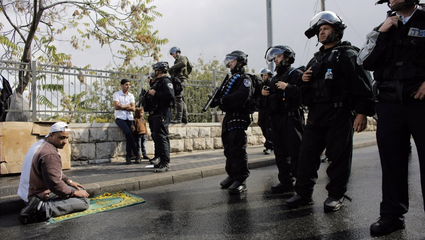 A Palestinian man prays near Israeli police during Friday prayers in the East Jerusalem neighbourhood of Wadi al-Joz on October 31, 2014. Israeli police declared an age limit on Friday for Palestinians wanting to enter the Old City, only allowing males ab