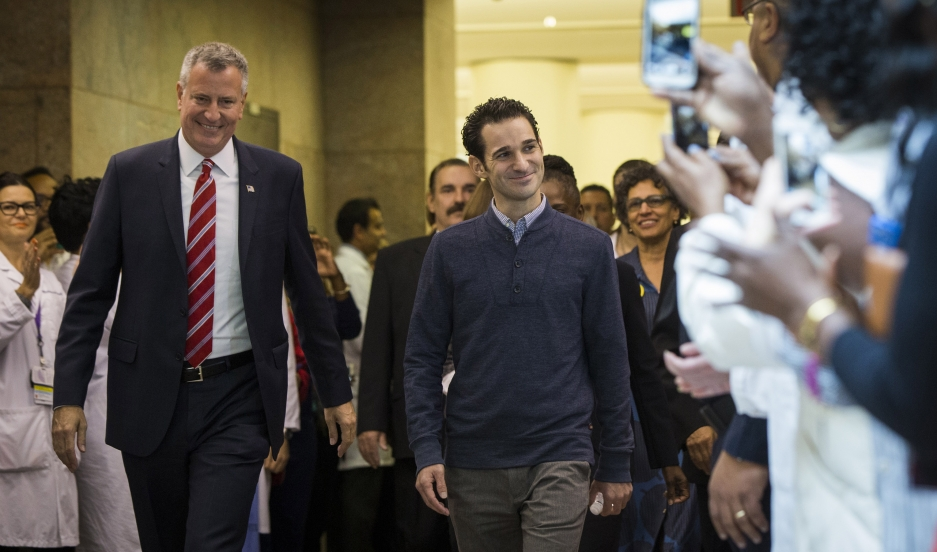 New York Mayor Bill de Blasio walks with Dr. Craig Spencer, at right, as he is discharged from Bellevue Hospital after being declared free of the Ebola virus on November 11, 2014.