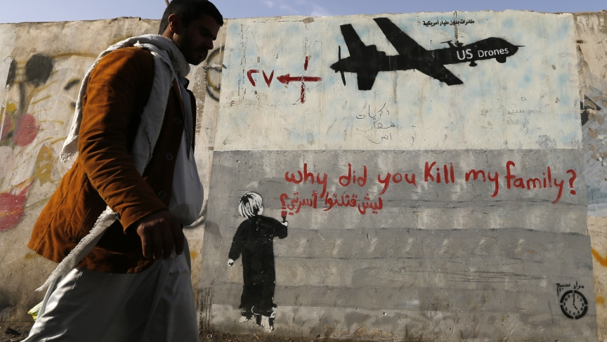 A man walks past graffiti denouncing US drone strikes in Yemen painted on a wall in Sana'a on November 13, 2014.