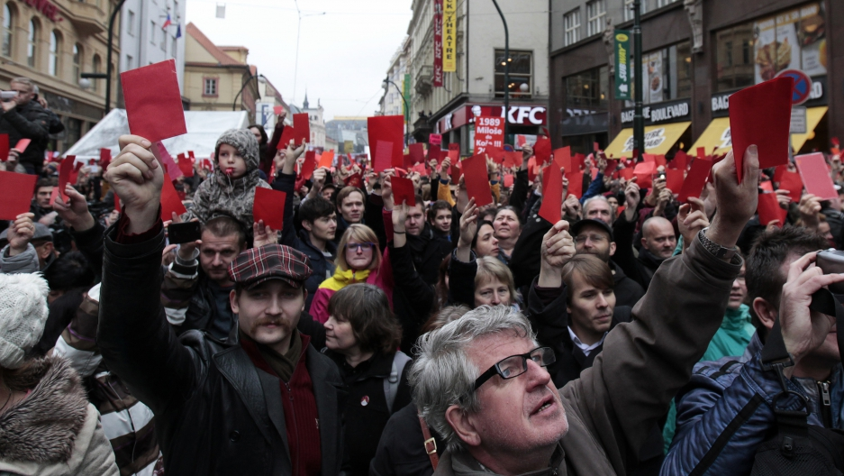 Protesters in Prague show symbolic red cards to Czech President Milos Zeman on the anniversary of the Velvet Revolution in 2014.