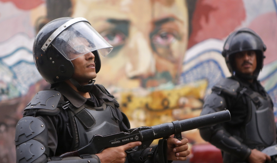 Riot police walk along Mohamed Mahmoud Street, near Cairo's Tahrir Square, in front of murals representing people killed during Egypt's uprising.