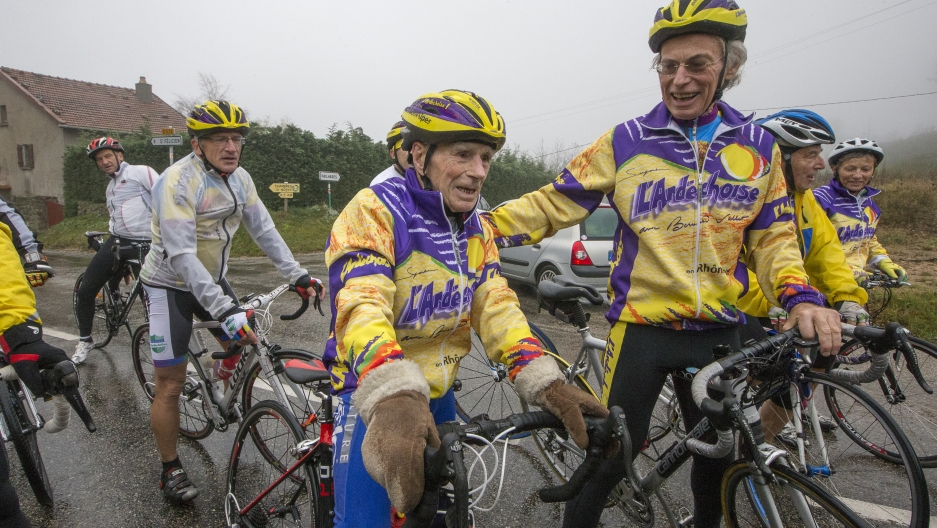 Robert Marchand (C), 103 years-old, speaks with riders as he makes his way along the Robert Marchand pass