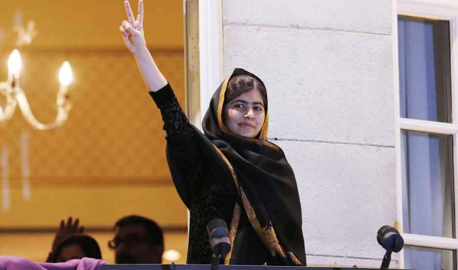 Nobel Peace Prize winner Malala Yousafzai flashes the peace sign from the balcony of the Grand Hotel in Oslo on December 10, 2014.