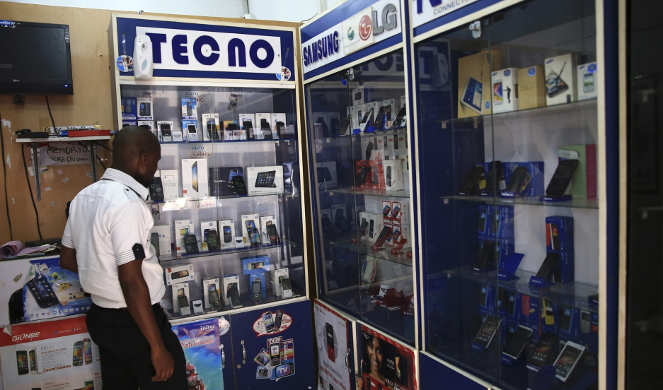 A man looks at smartphones on display at a shop at Wuse II business district in Abuja December 9, 2014.