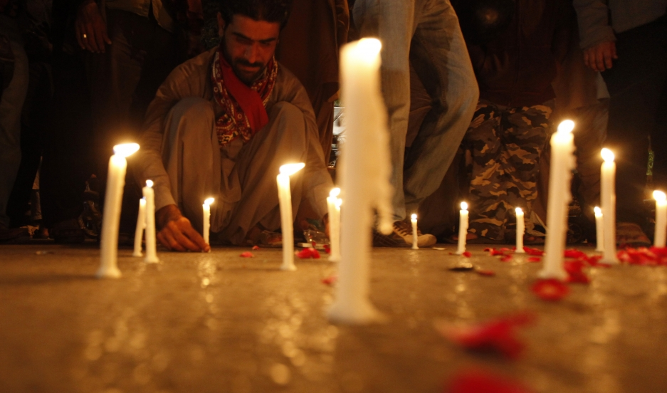 A man lights candles to mourn the victims from the Army Public School in Peshawar, which was attack by Taliban gunmen, in Karachi, December 16, 2014.