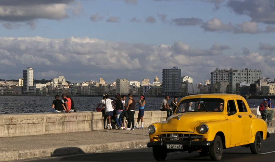 Youth sit on Havana's El Malecon seafront bolulevard December 17, 2014.