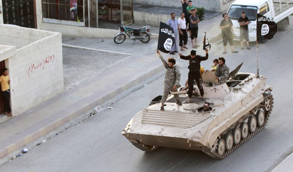 Militant Islamist fighters hold the flag of ISIS while taking part in a military parade along the streets of northern Raqqa province in this June 30, 2014 file photo.