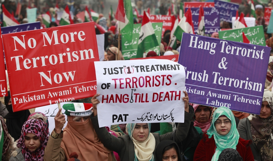 Supporters of Pakistani political party Pakistan Awami Tehreek hold signs to condemn the attack by Taliban gunmen on the Army Public School in Peshawar during a rally in Lahore on December 21, 2014.