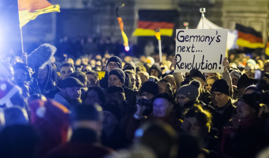 """A woman holds a sign during a demonstration organised by anti-immigration group PEGIDA, a German abbreviation for """"Patriotic Europeans against the Islamisation of the West"""", in Dresden December 22, 2014."""