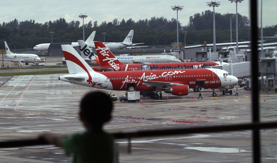 A child looks on at a viewing gallery overlooking AirAsia planes on the tarmac at Changi Airport in Singapore December 29, 2014.