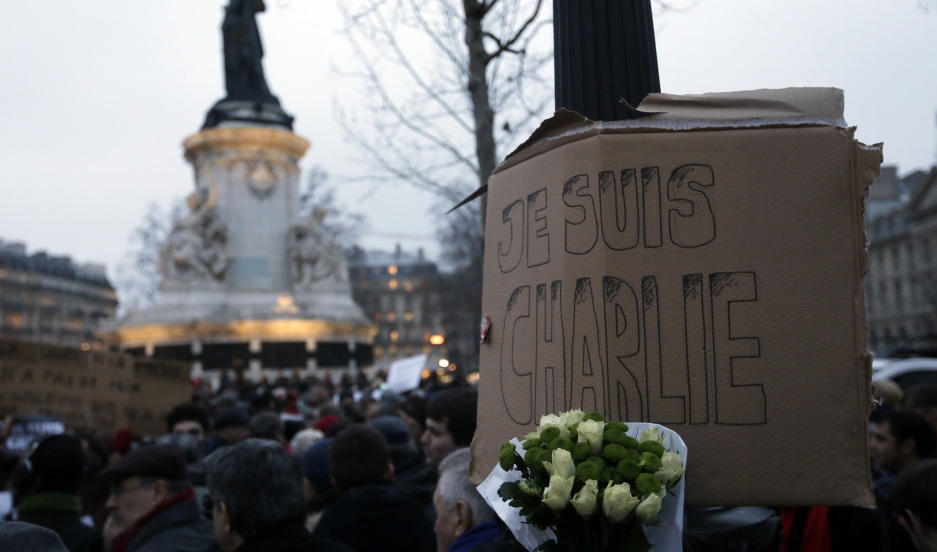 "A bouquet of roses is seen near a placard reading ""I am Charlie,"" displayed to pay tribute during a gathering at the Place de la Republique in Paris on January 7, 2015, following a shooting by gunmen at the offices of weekly satirical magazine Charlie Heb"