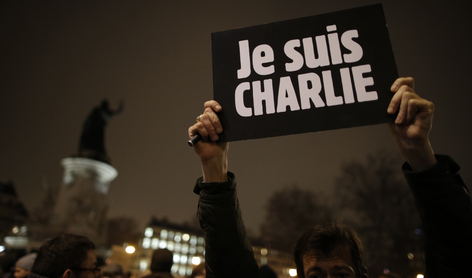 "A man holds a placard which reads ""I am Charlie"" to pay tribute during a gathering at the Place de la Republique in Paris on the night of January 7, 2015, following a shooting by gunmen at the offices of the magazine."