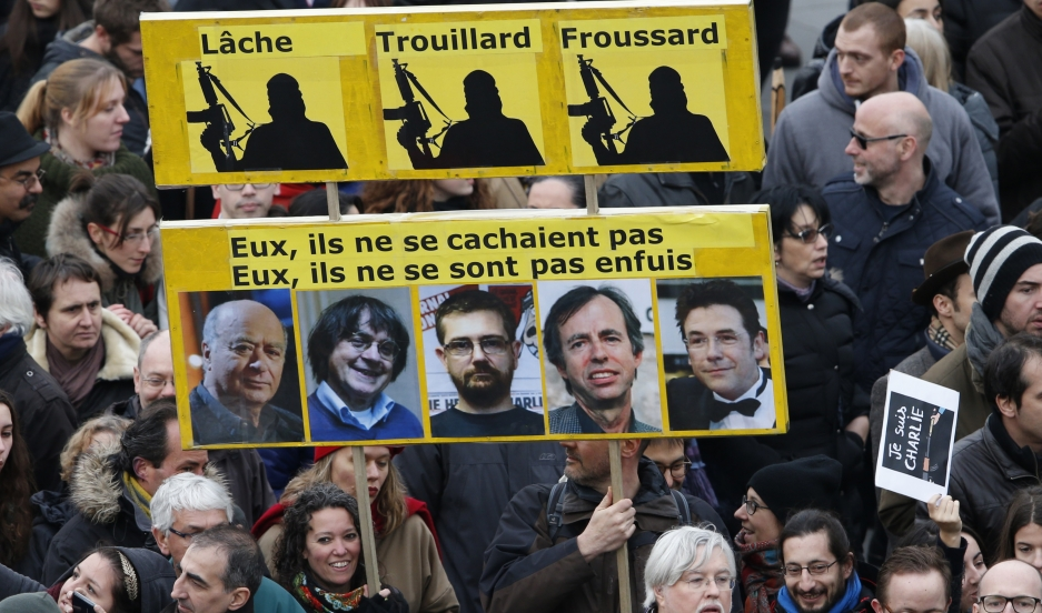 "Citizens carrying a placard reading ""Coward, Chicken, Yellow-Belly (top) and They, didn't hide. They they did not run (Bottom)"" take part in a Hundreds of thousands of French citizens solidarity march (Marche Republicaine) in the streets of Paris January"