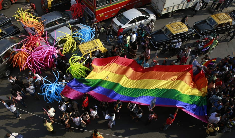 Participants holding a rainbow flag pass through a junction during a gay pride parade, which is promoting gay, lesbian, bisexual and transgender rights, in Mumbai, January 31, 2015.