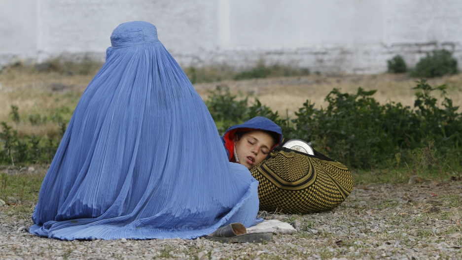 An Afghan refugee woman sits with her sleeping child as they wait with others to be repatriated to Afghanistan, at the United Nations High Commissioner for Refugees office on the outskirts of Peshawar, Pakistan, Feb. 2, 2015.