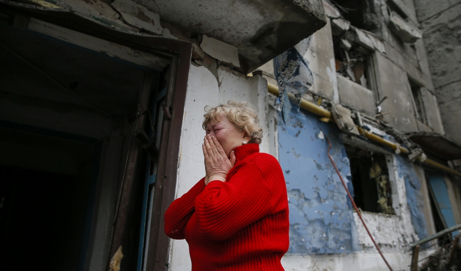 A woman takes stock of the damage to an apartment block, hit by shelling in a small town near Debaltseve, Ukraine on February 2, 2015.
