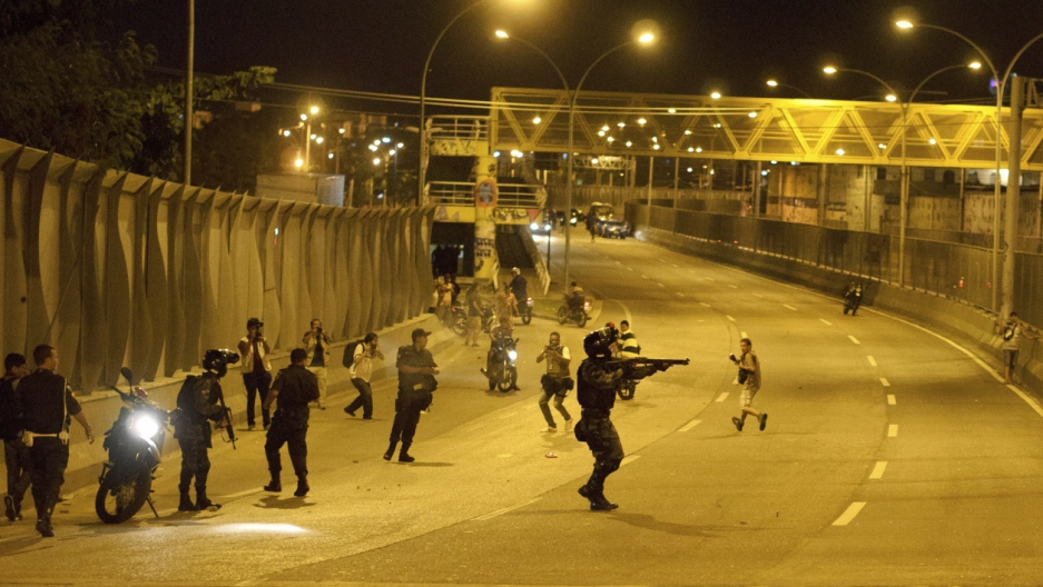 Policemen take positions during a shooting with suspected drug gangs on Linha Amarela highway near the Maré favela complex in Rio de Janeiro on Feb. 23, 2015.