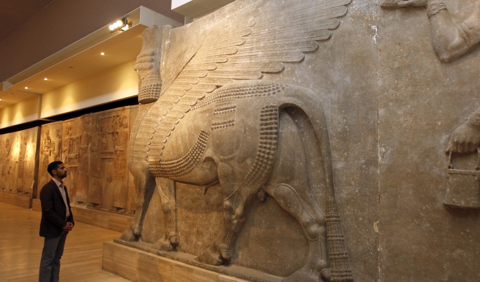 A man looks at an ancient Assyrian statue of a winged bull with a human head at the Iraqi National Museum in Baghdad on February 28, 2015.