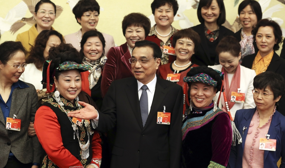 Chinese Premier Li Keqiang (C) poses with female delegates at the annual session of the National People's Congress (NPC) on International Women's Day in Beijing on March 8, 2015.
