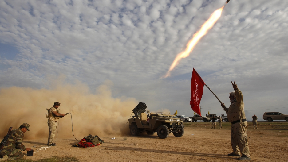 Shi'ite fighters launch a rocket during clashes with Islamic State militants on the outskirts of al-Alam March 8, 2015.