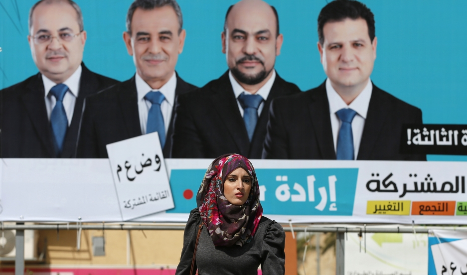 A woman walks past a Joint Arab List campaign billboard. Four Arab-Israeli political parties have united for the first time, making the group the third-largest political faction in the Knesset.