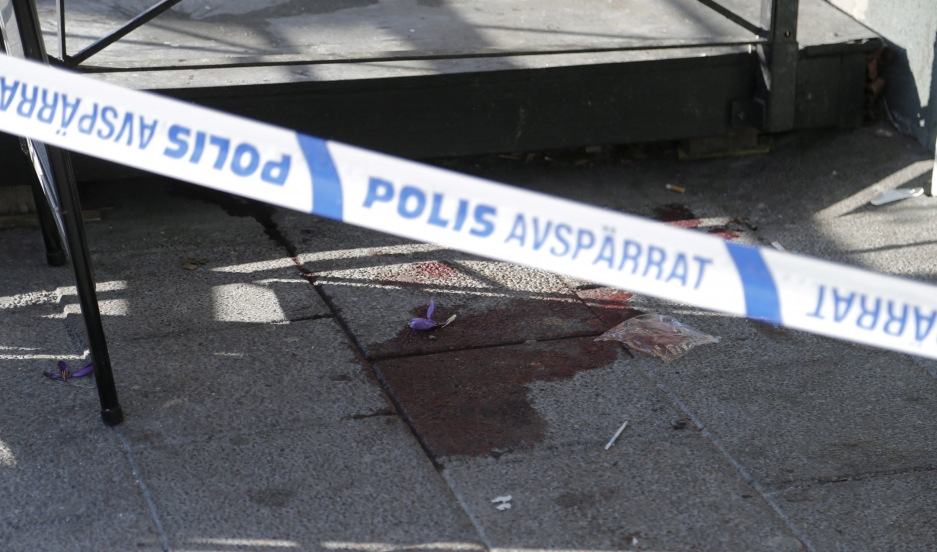 A bloodstain is seen behind police barrier tape at the scene of a fatal shooting in Gothenburg, March 18, 2015.