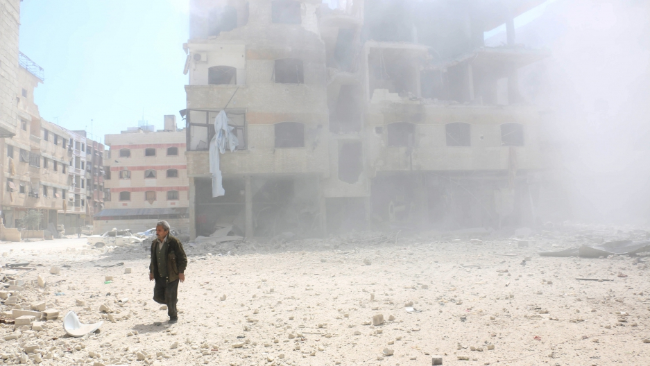 A man walks amid rubble of damaged buildings after what activists said was a mortar shell thrown on an area after air strikes by forces loyal to Syria's President Bashar al-Assad in Ain Tarma, in Eastern Ghouta, a suburb of Damascus, on April 5, 2015