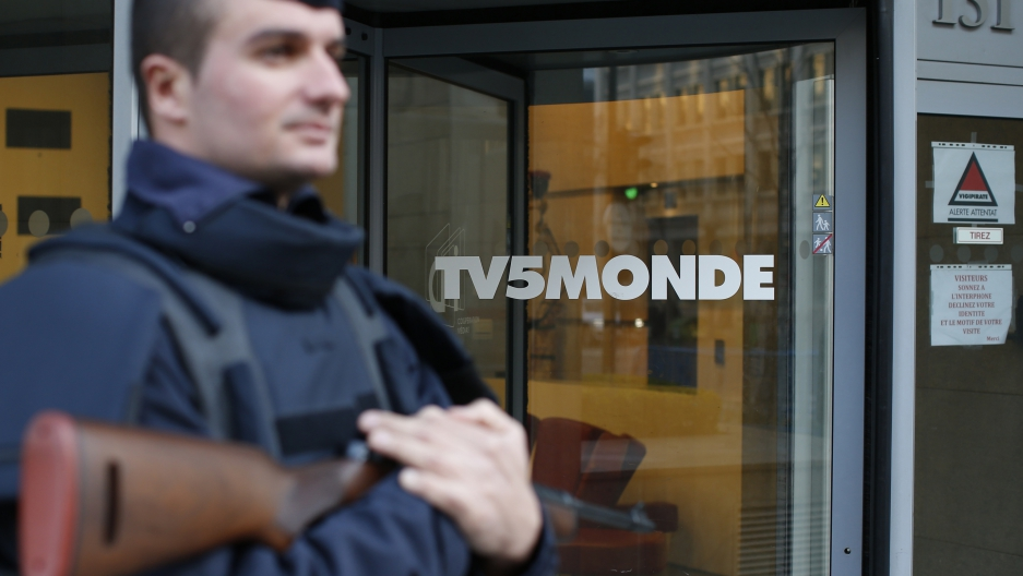 A police officer stands guard in front of the main entrance of French television network. The network is now believed to have been hacked by a Russian group linked to the hackers who have leaked emails from the Hillary Clinton campaign.