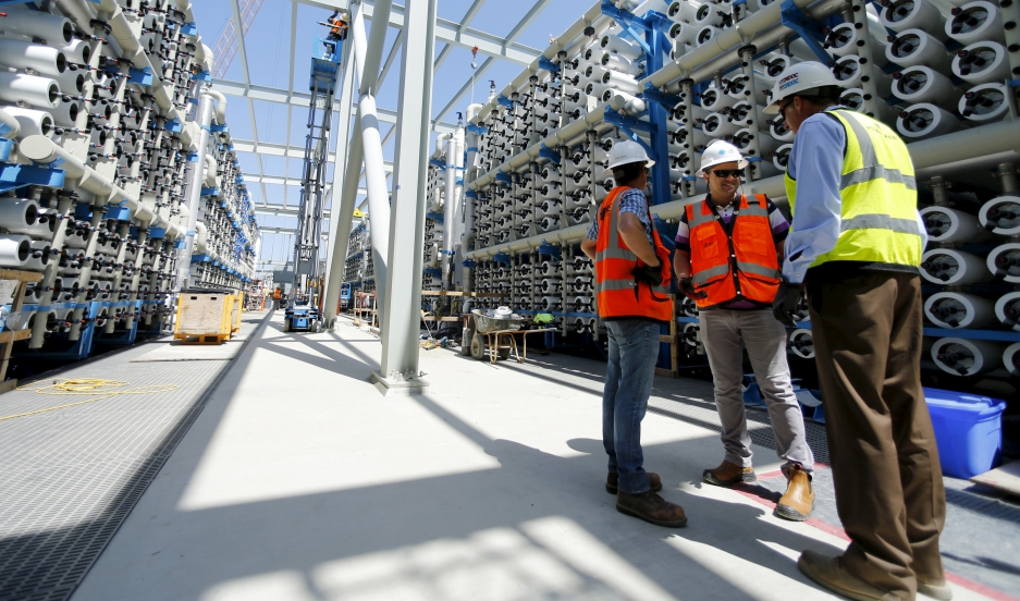 Poseidon Water employees stand between rows of reverse osmosis filters at the Western Hemisphere's largest seawater desalination plant, currently under construction in Carlsbad, California.