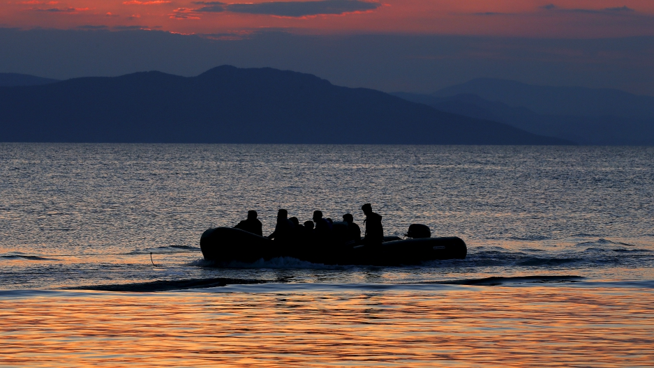 A dinghy with Syrian refugees is towed by a Greek coast guard patrol boat into the port on the Greek island of Kos, following a rescue operation in a part of the Aegean Sea between Turkey and Greece, early May 31, 2015.