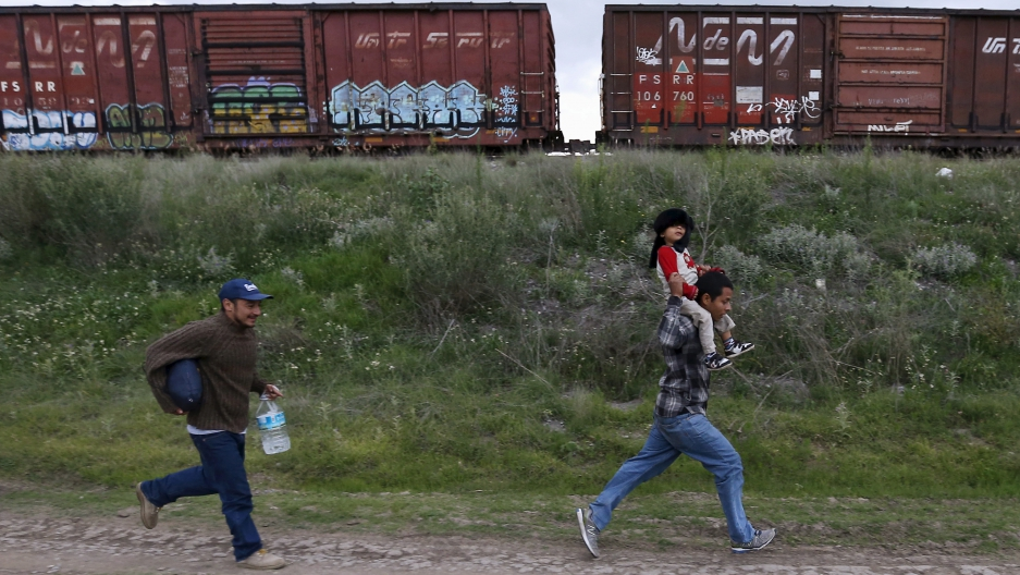 A Salvadoran father carries his son tries as he tries to board a train with another immigrant and head to the Mexican-U.S. border, in Huehuetoca, near Mexico City.