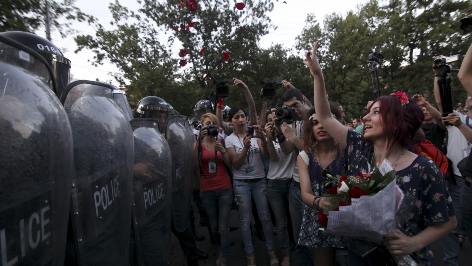 A protester throws rose petals in front of a line of riot police during an #ElectricYerevan protest in Armenia
